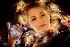Een jonge die vrouw door lichten wordt omringd Stock Foto