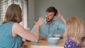Een jonge donker-haired vader heeft een gesprek met zijn mooie vrouw bij de keukenlijst Langzame Motie stock footage