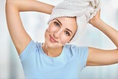 Een jonge donkerbruine die vrouw met een handdoek om haar hoofdholdi wordt verpakt Royalty-vrije Stock Foto
