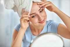 Een jonge donkerbruine die vrouw met een handdoek om haar hoofdholdi wordt verpakt Stock Foto