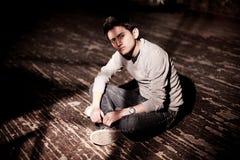 Een jonge donkerbruine mensenzitting op een houten vloer Stock Afbeeldingen