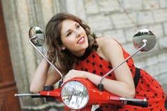 Een jonge donkerbruine vrouw in een rode kleding op een autoped royalty-vrije stock foto's