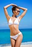 Een jonge donkerbruine vrouw in een wit zwempak op het strand royalty-vrije stock foto