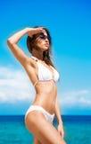 Een jonge donkerbruine vrouw in een wit zwempak op het strand royalty-vrije stock afbeelding
