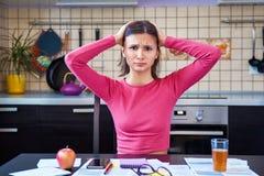 Een jonge donkerbruine vrouw in keuken greep haar hoofd van gezien onkostenrekeningen stock fotografie