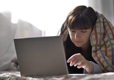Een jonge donkerbruine vrouw ligt onder een deken en typt in laptop stock afbeelding