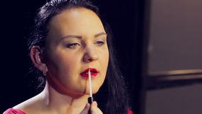 Een jonge donkerbruine vrouw past een glans op haar lippen met een borstel toe stock video