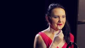 Een jonge donkerbruine vrouw past een glans op haar lippen met een borstel toe stock videobeelden
