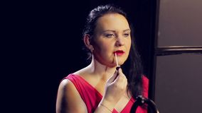 Een jonge donkerbruine vrouw past een glans op haar lippen met een borstel toe Close-up stock videobeelden