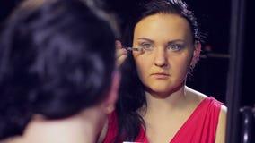 Een jonge donkerbruine vrouw in een rode kleding voor een spiegel maakt oogmake-up met lichte schaduwen met een borstel stock videobeelden