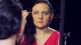 Een jonge donkerbruine vrouw in een rode kleding voor een spiegel maakt oogmake-up met lichte schaduwen met een borstel stock video
