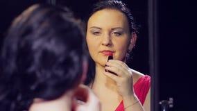 Een jonge donkerbruine vrouw in een rode kleding voor een spiegel schildert haar lippen met heldere rode lippenstift stock video