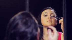 Een jonge donkerbruine vrouw in een rode kleding voor een spiegel zet mascara op haar wimpers stock video