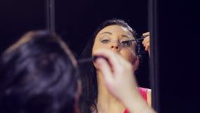 Een jonge donkerbruine vrouw in een rode kleding voor een spiegel zet mascara op haar wimpers stock footage
