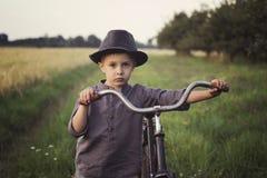 Een jonge, droevige jongen gekleed in een retro stijl, stelt een oude fiets in het platteland in werking stock foto