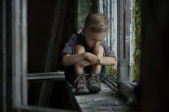 Een jonge, droevige jongen gekleed in een retro stijl, zit hij op de vensterbank van een oud, verlaten huis stock foto's