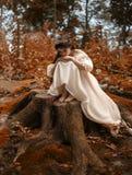 Een jonge, droevige prinses met zeer lang haar zit op een grote stomp van een oude boom en wacht op haar prins Het meisje heeft a royalty-vrije stock afbeeldingen