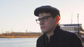 Een jonge, elegant geklede mens bevindt zich door de rivier en bekijkt zorgvuldig in de afstand, krabbend het traliewerk stock video