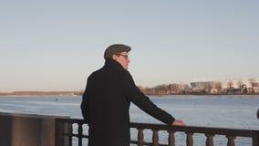 Een jonge, elegant geklede mens bevindt zich door de rivier en bekijkt zorgvuldig in de afstand, krabbend het traliewerk stock footage