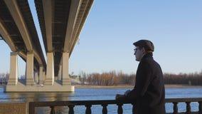 Een jonge, elegant geklede mens bevindt zich door de rivier en bekijkt zorgvuldig in de afstand, krabbend het traliewerk stock videobeelden