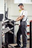 Een jonge en aantrekkelijke werktuigkundige glimlacht terwijl het werken bij de autodienst gebruikend een computer royalty-vrije stock afbeelding
