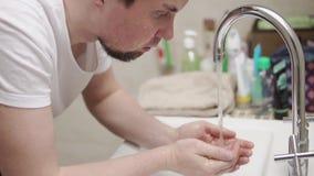 Een jonge en gebaarde mens wast zijn gezicht onder de kraan in de badkamers stock videobeelden