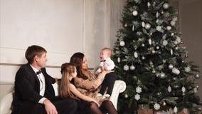 Een jonge en gelukkige familie in feestelijke kostuumsspelen met hun kleine zoon dichtbij de Nieuwjaarboom stock footage