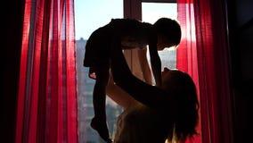 Een jonge en gelukkige moeder houdt haar kind naast het venster De zon` s stralen gaan door het venster over Het gelach stock video