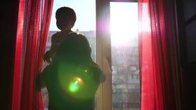 Een jonge en gelukkige moeder houdt haar kind naast het venster De zon` s stralen gaan door het venster over Het gelach stock videobeelden