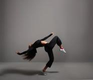 Een jonge en geschikte donkerbruine vrouw die in sportieve kleren dansen Stock Foto's