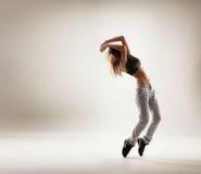 Een jonge en geschikte vrouw die in sportieve kleren dansen Royalty-vrije Stock Afbeelding