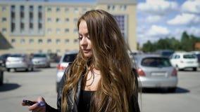 Een jonge en mooie vrouw die onderaan de straat onder auto's en moderne stadsfaciliteiten lopen, een dame kijkt gelukkig stock footage