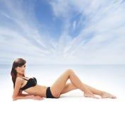 Een jonge en sexy brunette die in zwarte lingerie leggen Stock Foto's