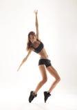 Een jonge en sportieve vrouw die in lichte kleren dansen Stock Afbeelding