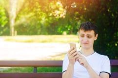 Een jonge Europese kerel zit op een bank in een stadspark en maakt een grappig gezicht onderzoekend de telefoon Het concept extre stock fotografie