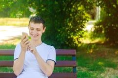 Een jonge Europese kerel zit op een bank in een stadspark en richt een vinger op de telefoon Een mens glimlacht het bekijken de t stock afbeeldingen