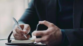 Een jonge Europese mens die, en nota's in café denken nemen door het venster Formele Slijtage Succesvol bedrijfsleven, stock footage