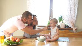 Een jonge familie brengt tijd in de keuken door, zet de papa bloem op de neus van zijn dochter Gelukkig familieconcept stock videobeelden