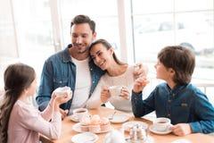 Een jonge familie kwam in een koffie samen stock foto's