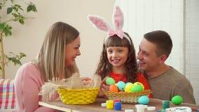 Een jonge familie lacht en toont gelukkig paaseieren aan de camera op de lijst is een mand met paaseieren, verven en stock video