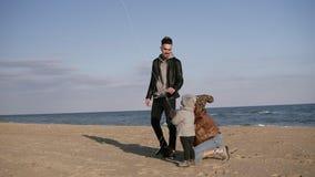 Een jonge familie met hun kleine zoon verenigt zich op de kustlijn dichtbij het overzees Spelend met een vlieger, een mens stock video