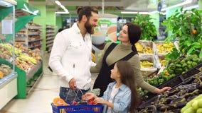Een jonge familie met een leuke dochter koopt groenten in de supermarkt stock videobeelden