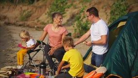Een jonge familie schikte een daglunch met een tent dichtbij het overzees op een zandig strand stock video
