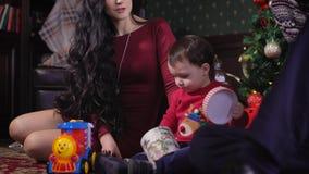 Een jonge familie treft thuis voor Kerstmis voorbereidingen Vrouw met haar echtgenoot en kind in prachtig verfraaide Kerstmis stock video