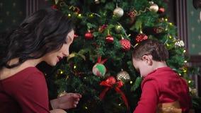 Een jonge familie treft voor Kerstmis in het huis voorbereidingen Langharig brunette die de Kerstboom verfraaien Het jonge geitje stock footage
