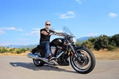 Een jonge fietser die een aangepaste motorfiets berijden stock fotografie