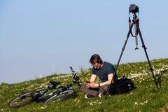 Een jonge fotograaf die de zonsondergang wachten stock fotografie