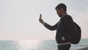 Een jonge fotograaf neemt fotoschoten op een smartphone, is een heer op zee stock videobeelden
