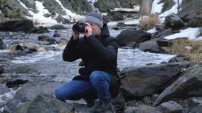 Een jonge fotograaf neemt landschapsfoto's stock video