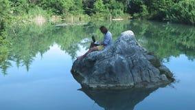 Een jonge freelance kerel zit op een steen in het midden van een meer met laptop Freelance concept Het werk aangaande reis draadl stock video